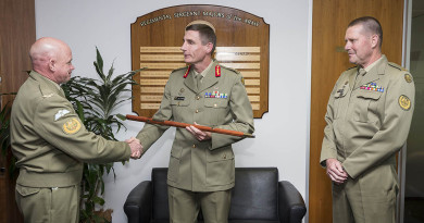 Chief of Army, Lieutenant General Angus Campbell receives the Army Pace Stick from Warrant Officer Dave Ashley at Army Headquarters in Canberra, watched by Warrant Officer Don Spinks