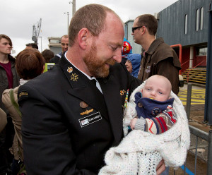 Chief Petty Officer Cryptologic Systems Sean Hardy holds his son for the first time. Photo by Able Seaman Tom Gibson.