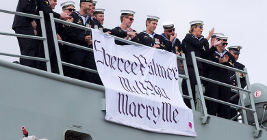 Leading Seaman Aviation Technician Avionics Warwick Douglas, surrounded by his ship mates, displays a banner proposing to his partner who is waiting on the wharf as HMAS Newcastle returns home from a successful rotation in the Middle East. SHE SAID YES! Photo by Able Seaman Tom Gibson
