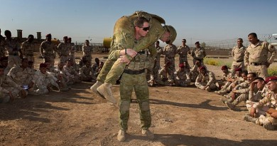 Australian Army trainer Corporal Benjamin Wallis demonstrates how to carry an injured soldier correctly on battlefield during a first aid lesson at the Taji Military Complex, Iraq. Photo by Corporal Oliver Carter.