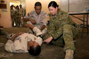Australian Army trainer Lieutenant Lisa Barker shows how to apply a combat application tourniquet to a simulated casualties' arm during a first aid lesson at the Taji Military Complex, Iraq. Photo by Captain Bradley Richardson