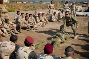Corporal Benjamin Wallis demonstrates how to drag a casualty during a first aid lesson at the Taji Military Complex, Iraq. Photo by Corporal Oliver Carter.