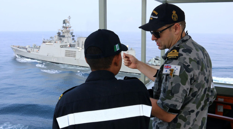 Indian Navy Lieutenant Aravirnd Bhat and Navigating Officer HMAS Sirius, Lieutenant Commander Peter Dargan, discuss the different approaches to at sea replenishment between the Australian and Indian Navies, whilst INS Shivalik prepares to conduct an approach for a practice replenishment. HMAS Sirius and INS Shivalik were taking part in AUSINDEX 15.