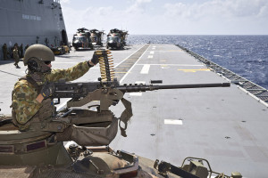 Australian Army soldier Lance Corporal Blake Simington loads a belt fed 50 calibre heavy machine gun on an Australian Light Armoured Vehicle onboard HMAS Canberra's flight deck, during Exercise Sea Raider.
