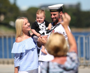 Leading Seaman Boatswains Mate Chris Bradshaw shares a moment with his partner and child before deploying to the Middle East on HMAS Darwin. Photos by Able Seaman Chantell Brown