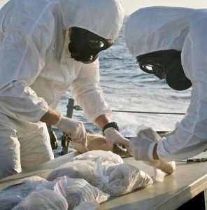 Crew members of HMAS Melbourne prepare to dispose of illegal narcotics seized from a fishing vessel in the Indian Ocean. Photos by Able Seaman Bonny Gassner