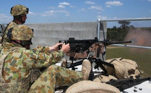 Australian Army soldier Corporal Michael Buxton fires a .50 calibre machine gun from a rooftop.