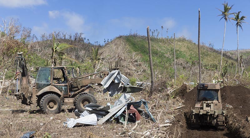 An Australian Army Backhoe gathers debris to be buried as a part of the clean up process of Operation Fiji Assist. Photo by Able Seaman Chris Beerens