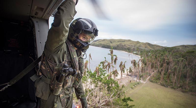 Helicopter Loadmaster, SGT Lyle Wooller looks over the landing zone from a RNZAF NH90 Helicopter lands as it comes in to land to deliver personnel and aid. NZDF photo