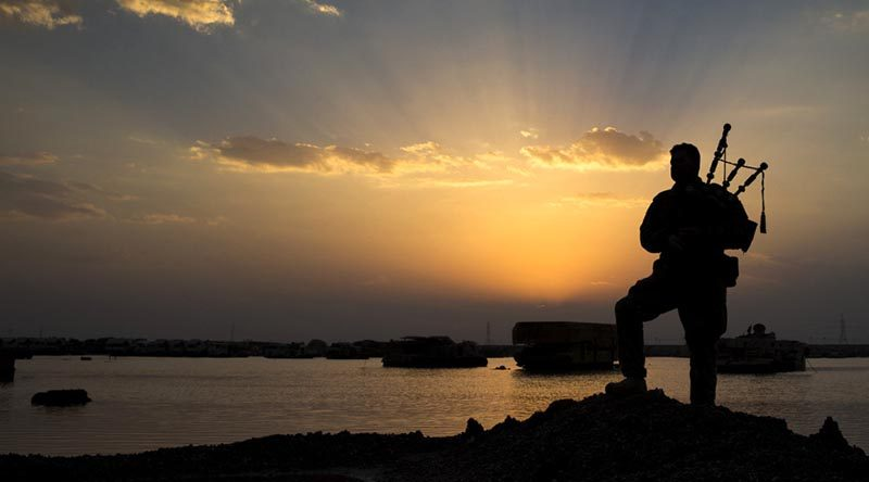 Australian soldier Corporal Kenneth Horton, of Task Group Taji, plays the bagpipes as the sun sets over the Taji Military Complex, Iraq. Photo by corporal Jake Sims