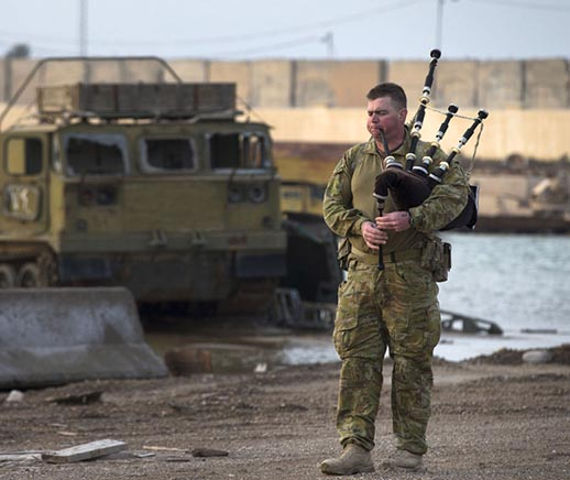 Australian soldier Corporal Kenneth Horton plays his bagpipes at the Taji Military Complex, Iraq. Photo by Corporal Jake Sims