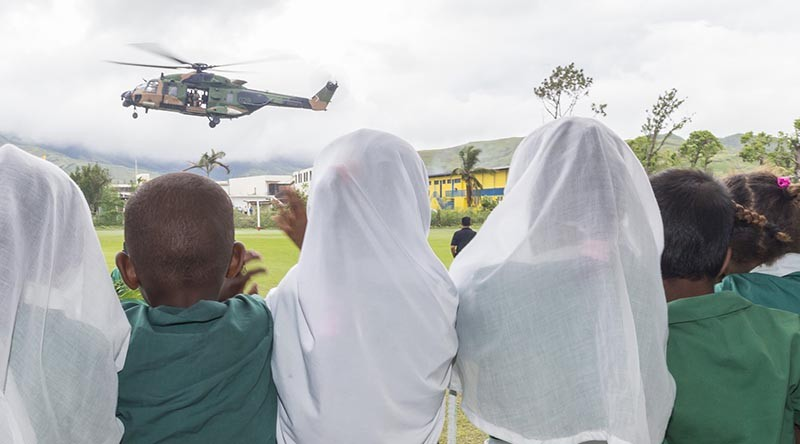 Students from the Rakiraki Muslim Primary School cheer as an Australian Army Taipan MRH-90 helicopter takes off for another mission during Operation Fiji Assist. Photo by Corporal Dan Pinhorn