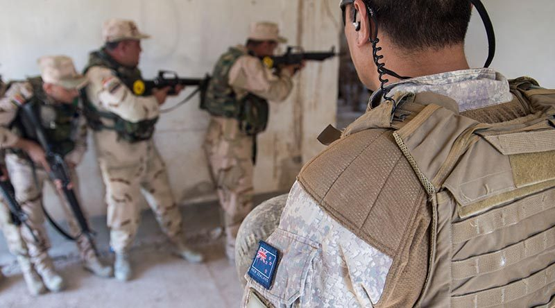 A New Zealand member of Task Group Taji, Training Task Unit supervises urban combat training for members of Iraq's 92nd Brigade at Taji Military Camp.