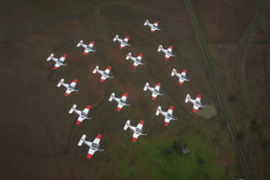 Above: Sixteen Pacific Aerospace CT-4B Airtrainers from the Basic Flying Training School fly in formation over Tamworth. Main Photo:Lieutenant Commander Andrew Kidd, a qualified flying instructor at the ADF Basic Flying Training School, follows the formation, Photos by Corporal Ollie Carter