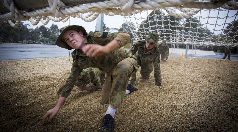 Australian Air Force Cadets Lachlan Bulmer tackles an obstacle during battle PT in the Canberra cold and rain at the Australian Defence Force Academy.