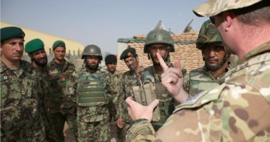 "Australian Army Major Christian Van Den Bosch shows Afghan National Army soldiers from the 205 Hero Corps an Australian-made ""Greengum"" radio-frequency jammer that disrupts signals that trigger improvised explosive devices. Photo by Corporal Max Bree"