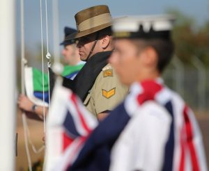 Corporal Owen Brady from Northern Command raises the Aboriginal Flag alongside the raising of the Australian National Flag and the Torres Strait Islander Flag, outside the Officers mess at Darwin's Larrakeyah Barracks to mark the unveiling of plaques and signage at Defence Bases across Darwin to recognise the Larrakeyah People as traditional custodians of the land.