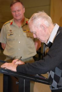 Jack Moore Junior signs over his family's donation to the Australian Army Museum of Military Engineering while Brigadier Wayne Budd looks on.