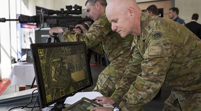 Australian Army officers Major Matt Haar (rear) and Major Shane Sarlin (front) try out the Sword sniper system during Army Innovation Day at the Australian Defence Force Academy in Canberra. Photo by Sergeant Janine Fabre.