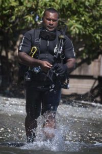 Royal Solomon Islands Police Force officer Simon Ariel Rihia collects explosive remnants of war from shallow waters at Hells Point. Photo by Sergeant Ricky Fuller.