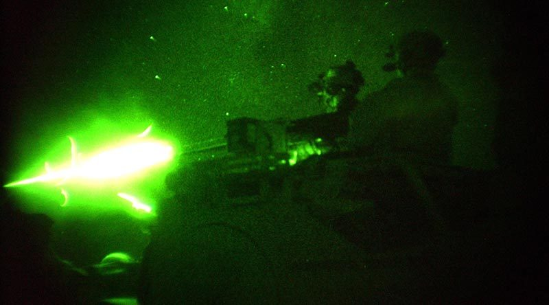 Special Forces Task Group (SFTG) members fire vehicle-mounted heavy weapons at night on a range at a Forward Operating Base (FOB) in Afghanistan. File photo – 2005 – by Sergeant John Carroll.