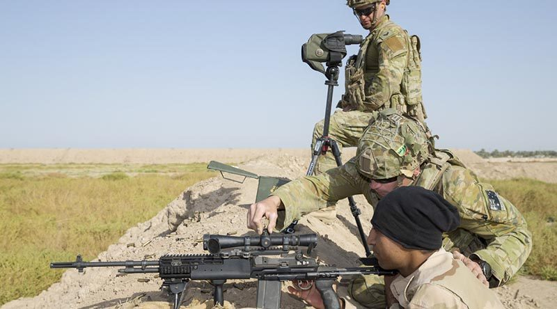 Australian soldier Corporal John Hatch (top) supervises as Private Lyndon Edwards adjusts the sights for an Iraqi Army soldier during marksmanship training at Taji Military Complex near Baghdad, Iraq. Photo by Leading Seaman Jake Badoir.