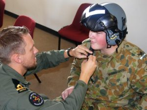 Cadet Corporal Andrew Paxton from 608 (Town of Gawler) Squadron, assisted by Sub Lieutenant Arvids Quinn, prepares for a helicopter flight.