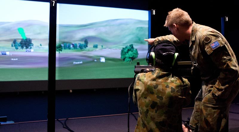 Lieutenant Dustin Gold assists a visitor at the Singleton Army WTSS (Weapon Training Simulation System) complex sight targets for a simulated 66mm anti-armour rocket. Photo by Leading Seaman Brenton Freind.