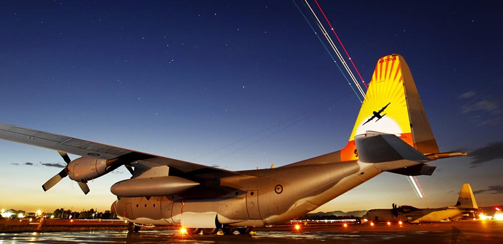 No. 37 Squadron C-130H Hercules A97-005 sports colourful tail art to to mark the type's retirement from Royal Australian Air Force service, on the RAAF Base Richmond flightline as a No. 34 Squadron Boeing Business Jet creates light trails in the sky. The tail art depicts a silhouette of a C-130H against a sunset, with the crests of No. 36 Squadron (Stallion) and No. 37 Squadron (Globe/Winged Water Carrier), representing the two units that had flown the C-130H. The RAAF operated a fleet of 12 C-130H Hercules from RAAF Base Richmond between 1978 until 2012. Photo by Corporal Amanda Campbell.
