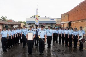 Some of the members of 608 Squadron after the parade, including: the Scroll Bearer, Cadet Corporal Casey Dibben (holding the frame), Parade Commander, Cadet Under Officer Aaron Musk (holding the sword), and Banner Bearer, Cadet Under Officer Hayden Skiparis (partially obscured, holding the banner).