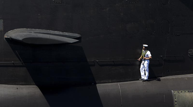 Leading Seaman Leigh Crutchley stands on the casing of HMAS Dechaineux as the boat comes alongside Fleet Base West after completing a busy few months at sea, 17 December 2016. Photo by Leading Seaman Lee-Anne Mack.