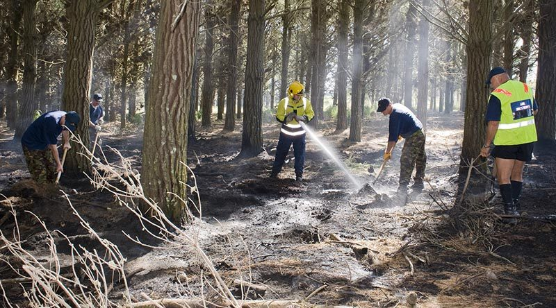 NZDF file photo: RNZAF Base Ohakea Fire Fighters putting out a smouldering fire in Raumai Air Weapons Range. The BCF (Base Contingency Force) assisted in turning over the soil to help cool down the area to stop the spread of the fire.