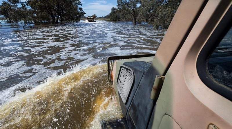 An Australian Army Unimog from 5th Brigade drives through flood waters during a mission to deliver sandbags to a NSW farmer. Photo by Corporal David Said.