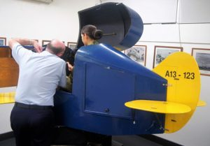 An Air Force Cadet receives instruction from an AAFC staff member before 'flying' Link Trainer A13-123.