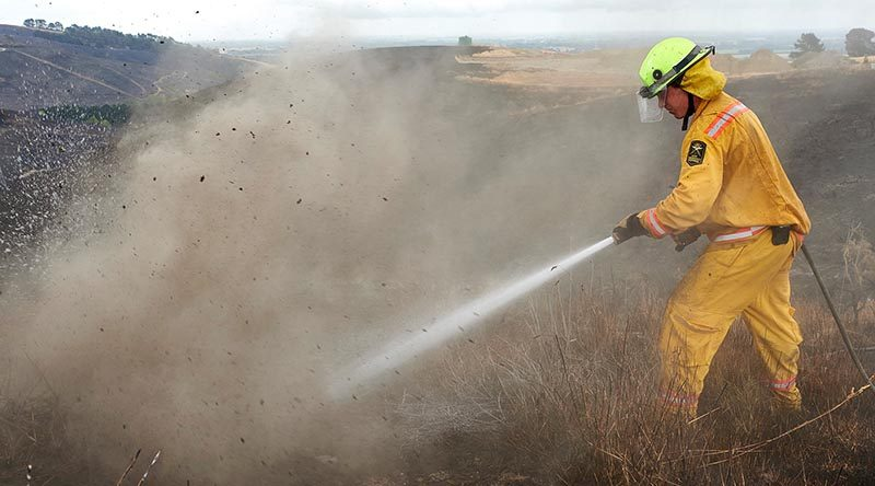 Firefighter Lieutenant Oli Barnfather of the New Zealand Army fights an underground hotspot on the Port Hills of Christchurch. NZDF photo.