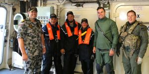 Three happy rough-seas warriors and their rescuers on HMAS Parramatta.