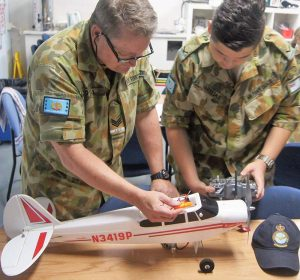 Sergeant (AAFC) Shayne O'Hara instructs Leading Cadet Haralambos Varelias (613 SQN) on binding the transmitter and receiver for a radio-controlled Super Cub aircraft.