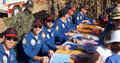 """Roulettes pilots autograph posters and give souvenirs to the public attending the 2017 Barossa Air Show, without noticing the photo-bomb by the Air Force Cadets' """"Ghillie Girl"""". Photo by Pilot Officer (AAFC) Paul Rosenzweig."""