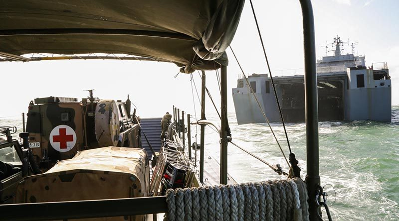 An Australian Army Bushmaster Protected Mobility Vehicle ambulance on an LCM8 landing craft exits the well dock of HMAS Choules. Photo by Able Seaman Bonny Gassner.