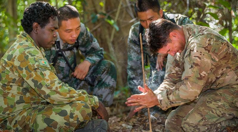 Australian Army soldier Lance Corporal Vinnie Rami (left) guides US Army soldier Sergeant First Class Adam Marques (right) through creating fire using the traditional 'drill' method, while two Chinese soldiers look and learn, during Exercise Kowari 2015 in the Daly River region, Northern Territory, Australia. Photo by Lance Corporal Kyle Jenner.