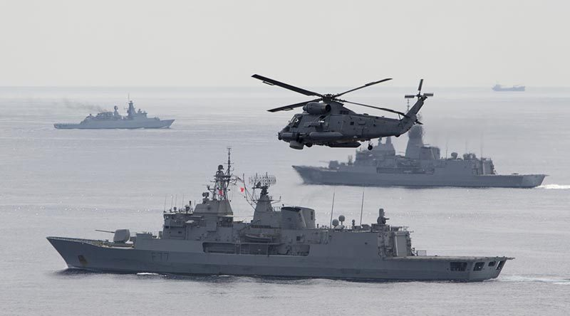A Royal New Zealand Navy Sea Sprite flies over the formation, as warships from Australia, Malaysia, Singapore and New Zealand conduct a Photo Exercise during Bersama Shield 2017. Photo by Leading Seaman Bradley Darrell.