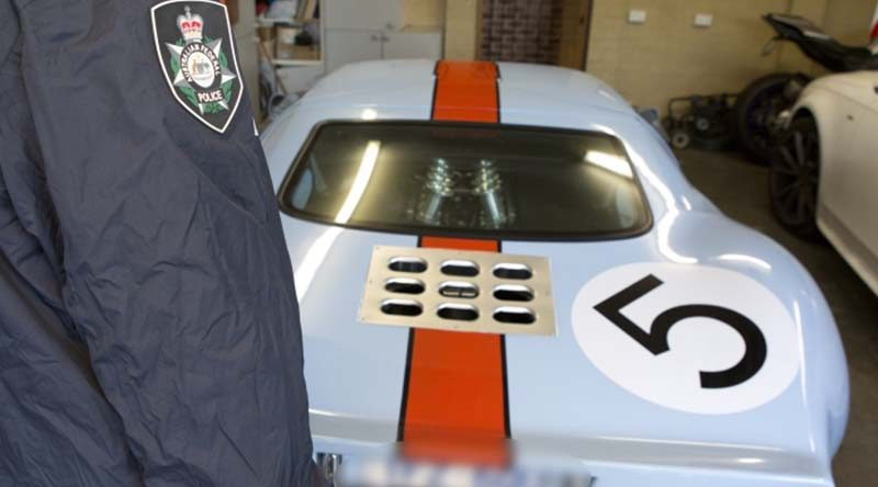 An AFP officer examines a luxury car seized in a raid on properties associated with a $165 million tax fraud. AFP photo.