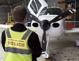 An AFP officer examines a aircraft seized in raids relating to a $165m tax fraud. AFP photo.