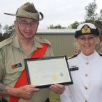 John Arnfield accepts a certificate of thanks for the Queensland National Serviceman's Pipe Band from TS Koopa's Lieutenant Jane Reptik.