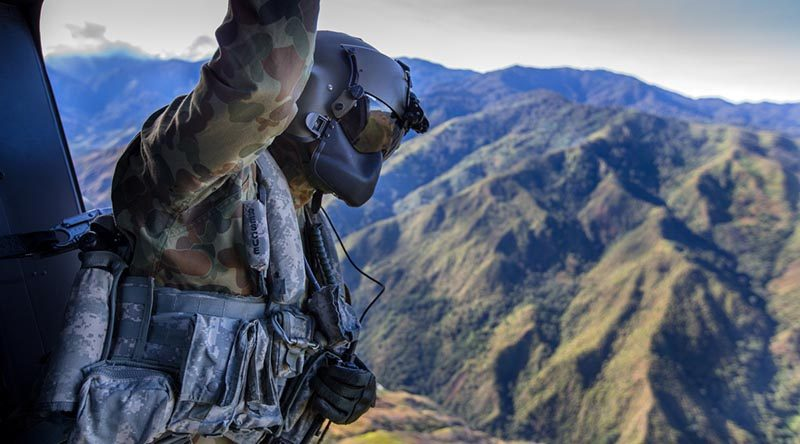 Corporal Rob Johnson, 5th Aviation Regiment, guides an MRH-90 helicopter for landing during Operation Hannah in Papua New Guinea. Photo by Corporal Jake Sims.