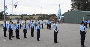 No 605 Squadron on parade at the Noarlunga Depot, with Cadet Under Officer Tahlia Sawtell as Parade Commander, Cadet Sergeant Christian Custodio (Banner Bearer) and Cadet Corporal Tanielle Edwards (Flight Commander), and the 6 Wing Band in the background. Image by Rick Fry.