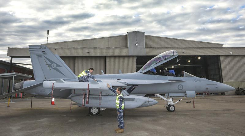Leading Aircraftwoman Aimee-Rose Carter and Leading Aircraftman Fletcher Moulton perform routine checks on a newly arrived EA-18G Growler at No. 6 Squadron, RAAF Base Amberley. Photo by Corporal Brenton Kwaterski.