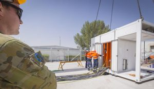 FIT-31 logistics officer Lieutenant Ben Carruthers watches as Datapod employees prepare power cabling for the new Containerised Data Centre at Camp Baird.