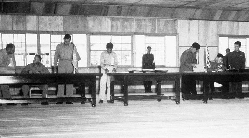 Delegates sign the Korean War Armistice on 27 July 1953. US DoD photo.