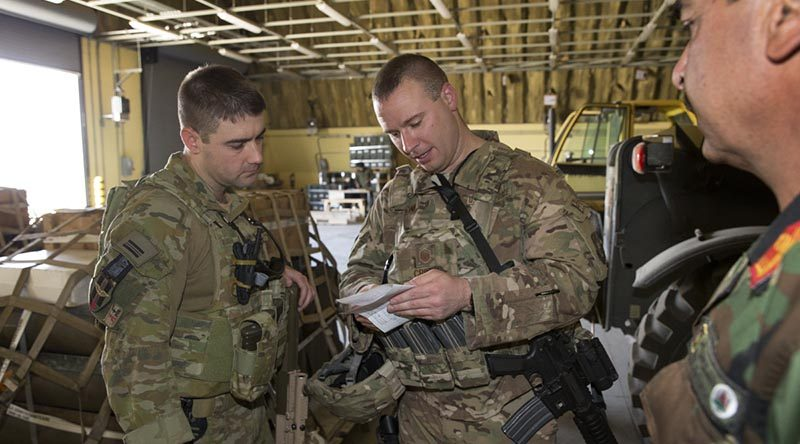 Armament Advisor to the Afghan Air Force Squadron Leader Nathan Gilmore (left) checks ammunition reserve levels with his colleagues at Hamid Karzai International Airport, Kabul, Afghanistan. Photo by Sergeant Ricky Fuller.